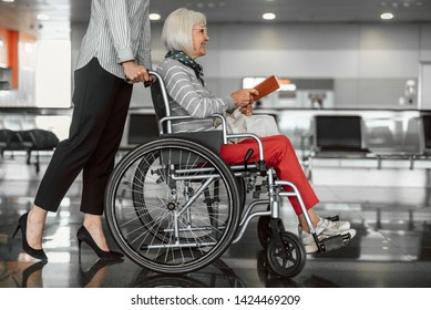Airport female officer helping old female on wheelchair to get boarding. Adult lady holding ticket and smiling