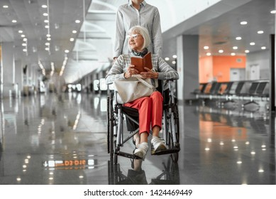 Airport female officer moving old female on disabled carriage through lobby. Mature lady in glasses holding ticket and smiling
