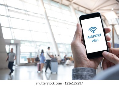 Airport free WiFi zone. Man using mobile smart mobile phone connecting airport free wifi, passenger walking with baggage as background, internet airport service