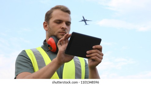 Airport Ground Serviceman Job Work Using Digital Tablet while Airplane Passing Overhead