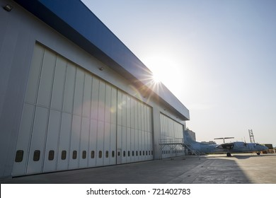 Airport hangar from the outside with big tall doors. Bright blue sky with sunlight.