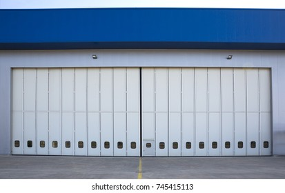 Airport hangar from the outside with big tall doors. Front view.