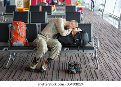 Airport lounge and people waiting for boarding. Body of male on foreground sleeping on his luggage lying in chair other people miscellaneous actions on background terminal interior with large windows