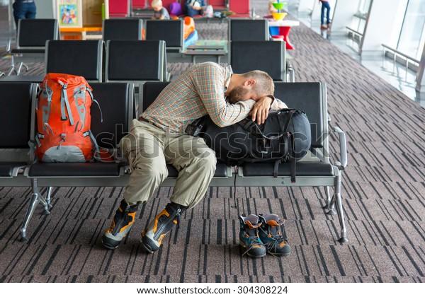 Flughafenlounge und Personen, die auf das Boarding warten. Körper von Männchen auf Vordergrundschlafen auf seinem Gepäck liegen im Stuhl andere Personen verschiedene Handlungen auf dem Hintergrund Terminalinnenraum mit großen Fenstern