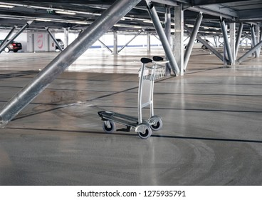 Airport luggage cart left in the middle of modern empty parking at international airport