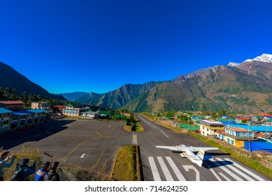 Airport in Lukla village with plane and mountains behind