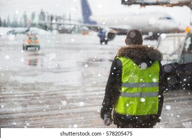 Airport manager standing under snowfall.