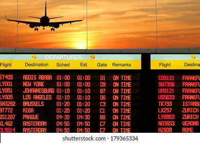 Airport outside window scene with silhouette of plane flying at orange sunset and title of  electronic display timetable of departures