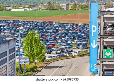 Airport parking lot with cars - parking garage with P sign aside