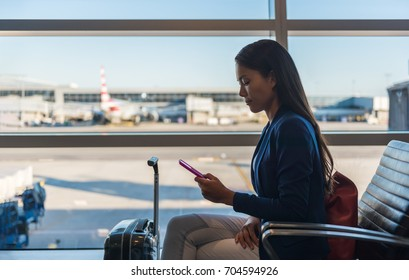 Airport phone travel woman using mobile phone in business class lounge waiting for plane flight texting sms message on smartphone. Technology and travel people frequent flying lifestyle.