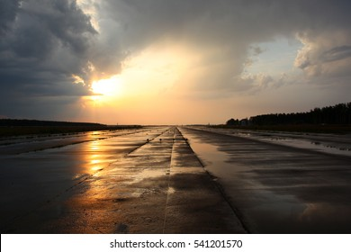 Airport runway after rain during sunset.