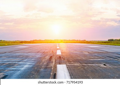 Airport runway airplanes with traces of rubber tires at dawn in the morning with sun glare