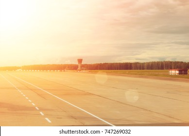 Airport runway with a forest at the background on cloudy day, toned background with copy space.