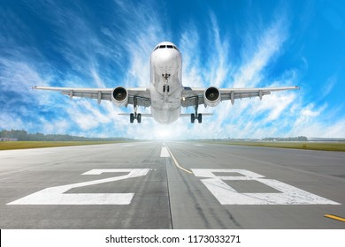 Airport runway number 28 and airplane take off to in horizon and picturesque cirrus clouds in the blue sky
