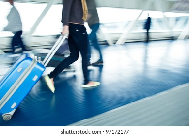 Airport rush: people with their suitcases walking along a corridor (motion blurred image; color toned image)