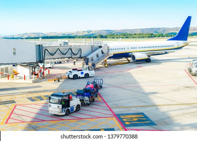 Airport scene, gangway to airplane, service loader cars carrying luggage by airfield, Madrid, Spain