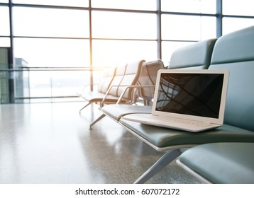 Airport seating with a laptop.