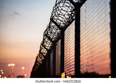 Airport security fence after sunset