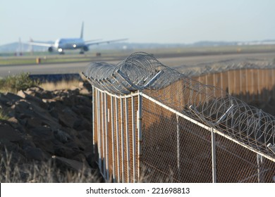 airport security mesh and barbed wire perimeter fence, with airliner.