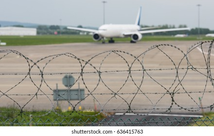 airport security mesh and razor wire perimeter fence with jet airliner on the runway in the background