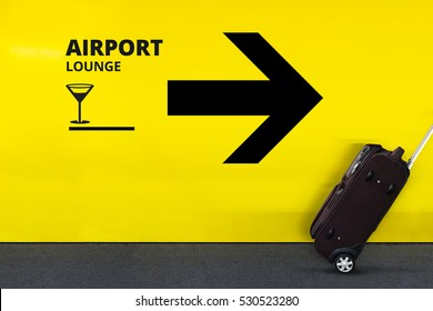 Airport Sign With Lounge Icon and Arrow with Moving Luggage in the Terminal on Yellow Wall