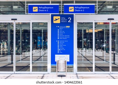 Airport terminal building gate entrance and automatic glass door with info text in german and english. Modern airport glass wall aisle window and door. Terminal entrance, automatic glass doors.