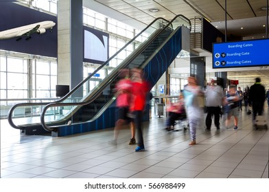 Airport terminal concourse with people moving along a corridor showing movement and activity