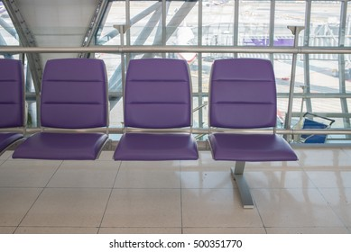 Airport terminal interior with rows of empty seats, city view and a parking by airplane.