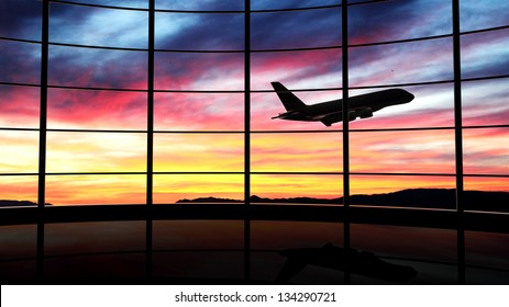 Airport terminal window with airplane flying at sunset