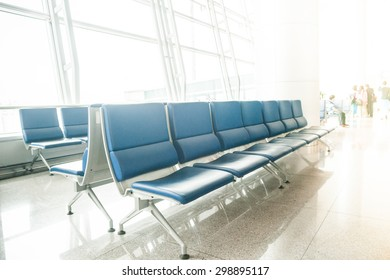 Airport waiting area with rows of blue seats. Background for topics of travel and business.