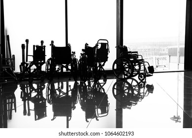 At the airport, in the waiting room, against the background of the window overlooking the aircraft and the runway, is a wheelchair, you can see its outlines.