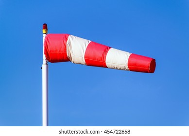 Airport windsock on clear blue sky background in windy weather indicate the local wind direction (also called: air sock, drogue, wind sleeve, wind cone)