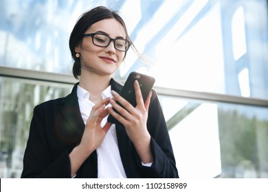 Airport woman on smart phone at gate waiting in terminal. Air travel concept with young casual business woman sitting with talking on the smartphone, carry-on hand luggage trolley. Beautiful young.