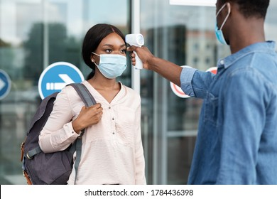 Airport Worker Checking Black Female Passenger's Temperature With Electronic Thermometer After Arrival, Covid-19 Outbreak Prevention