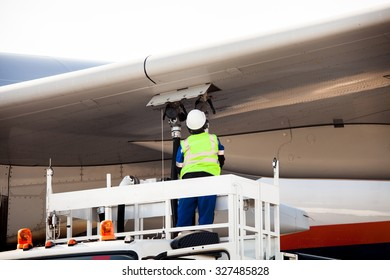 Airport worker refueling the aircraft