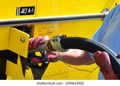 An airport worker refueling an aircraft with Jet A1 fuel, he is wearing gloves as the fuel is highly dangerous