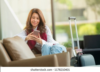 Airport Young female passenger holding smart phone device sitting in terminal hall while waiting for her flight.