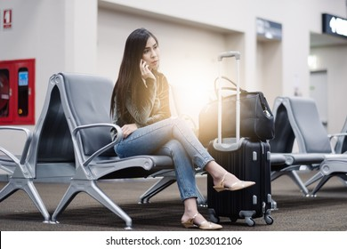 Airport Young female passenger on smart phone sitting in terminal hall while waiting for her flight