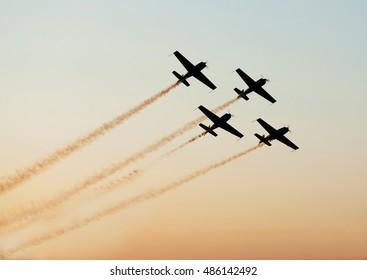 Airshow planes in star formation leaving smoke trails over sky