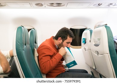 Airsickness. Man feels very bad on the air plane, using a sickness bag (also known as a sick sack, emesis bag, barf bag, vomit bag)