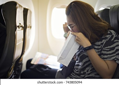 Airsickness. Woman feels very bad on the plane. Young woman is vomiting in the airplane with using a sickness bag.