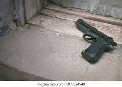 Airsoft gun on the old concrete wall background with copy space. Sport weapon ammunition.