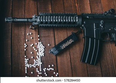 airsoft loader is on the table with a rifle and white balls