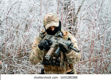 Airsoft man in camouflage uniform and machinegun with optical sight. Soldier in the winter forest. Horizontal photo side view