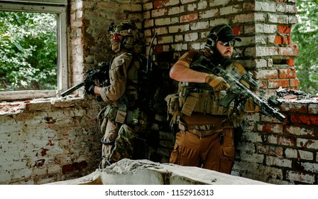 Airsoft men with guns stand back to back. Soldiers stand in to building looking to the windows
