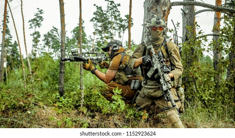 Airsoft men with guns stand back to back. Soldiers stand on hill and on call