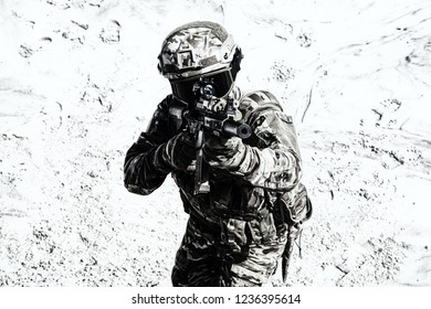 Airsoft player in camo combat uniform, protected with helmet and ballistic glasses, aiming with optical sight on army service rifle replica in sandy area desaturated shoot. War games participant
