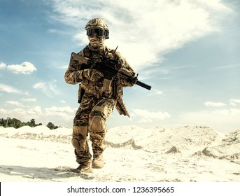 Airsoft player in camouflage uniform protected with helmet and ballistic goggles running with army service rifle replica in sandy area during military operation, war collisions or battle simulation