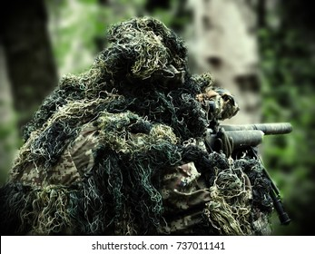 airsoft player with Ghillie Suit and sniper rifle