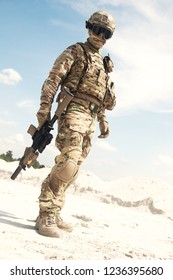 Airsoft player, military games participant in U.S. army infantry camouflage uniform, tactical mask, helmet and glasses, standing in desert area with combat service rifle or carbine replica in hands